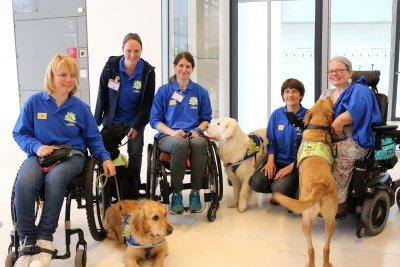 Sabine Häcker (2.v.r.), Vorsitzende von Hunde für Handicaps, und vier Vereinsmitglieder  zeigten, mit welchen Assistenzleistungen ihre Hunde sie im Alltag unterstützen.; Bildquelle: Jasmin Stoiber / Hunde für Handicaps